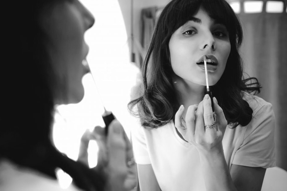 woman applying lipstick - black and white