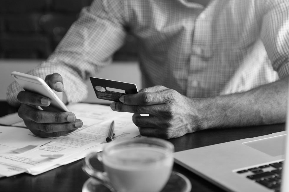Man with credit card and phone - black and white