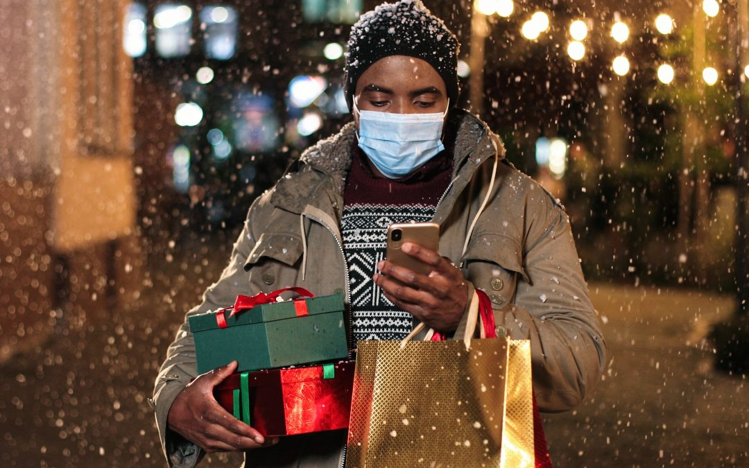 man shopping online on mobile phone holding gifts holidays 2021 advertising trends